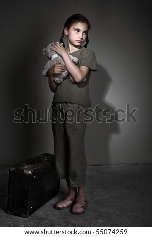 Little lonely girl with suitcase