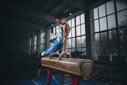 Little male gymnast training in gym, flexible and active. Caucasian fit little boy, athlete in sportswear practicing in exercises for strength, balance.