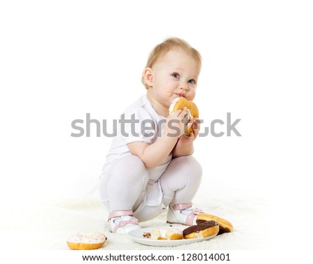 Little messy child eating doughnuts on a white background. - stock photo