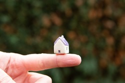 Little miniature house sitting on finger with green outdoor background, natural light. Tiny house movement, home ownership, property market ownership, carbon footprint concept idea
