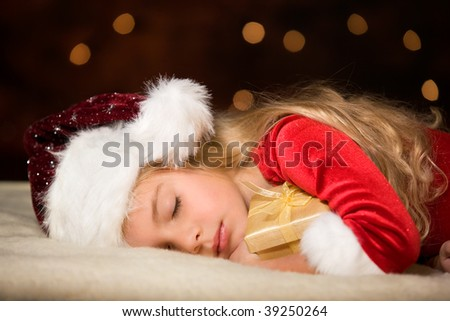 little miss santa asleep with a gift in her hand