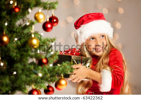 little miss santa shaking a gift to find out what is inside