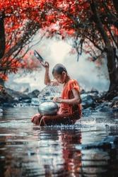 Little monk taking a bath at waterfall, Nong Khai, Thailand.