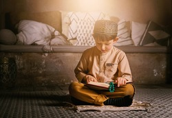 Little muslim boy in prayer cap and arabic clothes with rosary beads reading holy quran book praying to Allah, prophet Muhammad holy spirit religion symbol concept inside eastern traditional interior