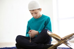 Little Muslim boy praying, indoors