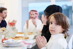 little muslim boy praying with traditional family before having iftar dinner together during a ramadan feast at home