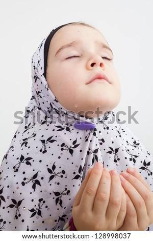 Little muslim girl praying holding her hands up