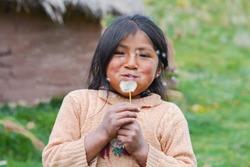 Little native american girl blowing dandelion flower.