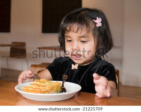 Little Native American girl getting ready to eat a slice of quiche in a coffee shop