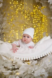 Little newborn baby boy lying in white clothes on bright background.