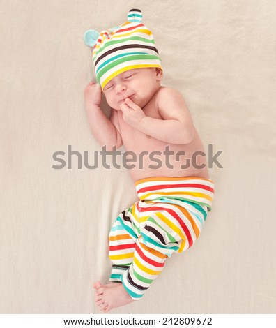 Little newborn baby dreaming on bed