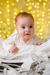 Little newborn baby girl lying in white clothes on bright background.