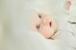 Little newborn baby girl lying in white clothes on white blanket background.