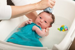 Little newborn baby having a bath