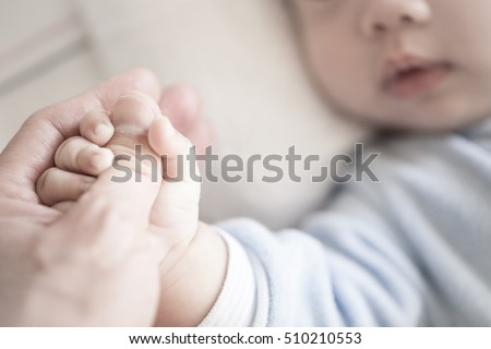 Little newborn baby holding parent's one hand, close-up macro shot. Focus on foreground. The touching and lovely moment. Concept of support, hope, love, bonding and care, hold on... #510210553