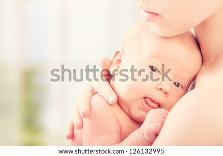 little newborn baby in the arms of mother