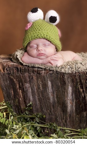 Little newborn dressed up as frog and sleeping on a tree stump