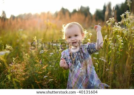 Little nice smiling baby walking in a meadow
