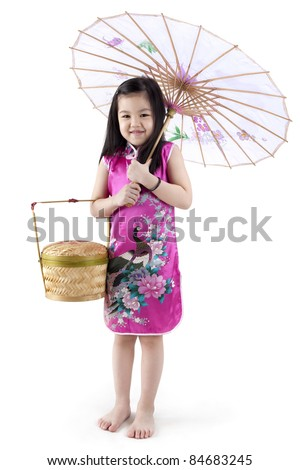 Little oriental girl in traditional Chinese dress cheongsam with umbrella and basket