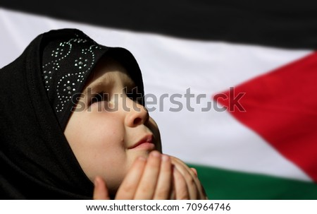 Little Palestine girl praying - Palestine flag in background