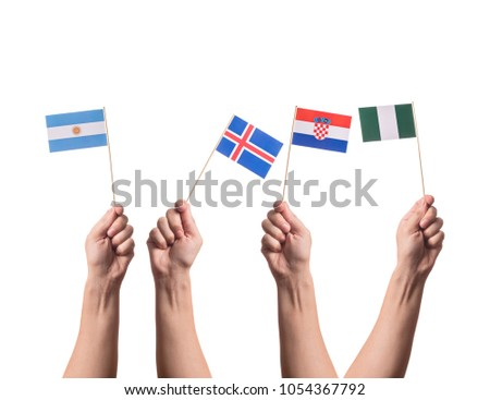 Little paper national flags in hands isolated on white background. Flags of national football teams of Argentina, Iceland, Croatia, Nigeria. World cup competitors in group D #1054367792