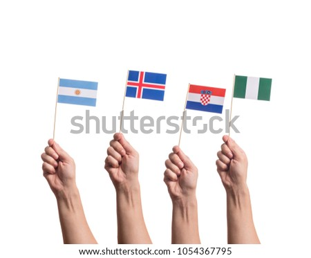 Little paper national flags in hands isolated on white background. Flags of national football teams of Argentina, Iceland, Croatia, Nigeria. World cup competitors in group D #1054367795