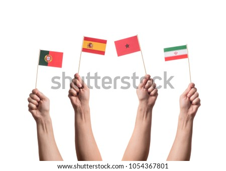 Little paper national flags in hands isolated on white background. Flags of national football teams of Portugal, Spain, Morocco, Iran. World cup competitors in group B #1054367801