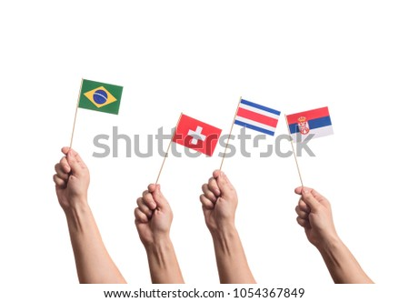 Little paper national flags in hands isolated on white background. Flags of national football teams of Brasil, Switzerland, Costa Rica, Serbia. World cup competitors in group E #1054367849