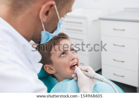 Little patient at dentist office. Top view of little boy sitting at the chair in dental office while doctor examining teeth
