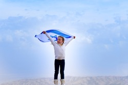 Little patriot jewish girl standing  and enjoying with the flag of Israel on blue sky background.Memorial day-Yom Hazikaron, Patriotic holiday Independence day Israel - Yom Ha'atzmaut concept.