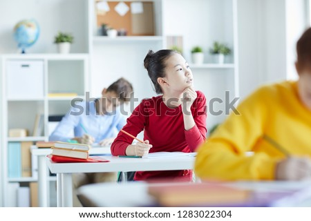 Little pensive girl looking through classroom window while sitting by desk and working individually