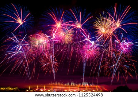 little people on the background of a huge Colorful fireworks #1125524498