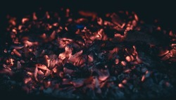 Little pieces of burning ember after the fire. Glowing incandescent embers texture. close up.