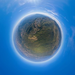 Little planet 360 degree sphere. Panorama of aerial view of cars driving on curved, zigzag curve road or street on mountain hill with green natural forest trees in rural area of Phu Tub Berk
