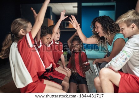 Little players and female coach at the locker room excited and ready for the match. Children team sport Photo stock ©