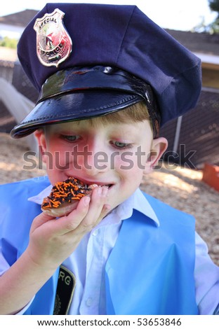 Little policeman eating a donut