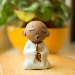 Little praying monk made of clay. Home decor element. calm and cute figure.