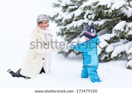 Little preschool boy and his mother playing with first snow in park