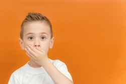 Little preschool boy covered her mouth with her hands. Keep it secret. Space for text. Concept of silence, no talking, I won't say anything. Emotional portrait of kid boy. Isolated on a yellow