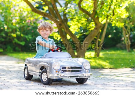 Little preschool boy driving big toy old vintage car and having fun, outdoors. Active leisure with kids on warm summer day.