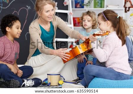 Little preschool girl holding teacher's guitar on music lesson #635590514