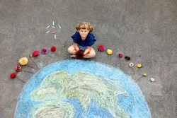 Little preschool girl with flowers and earth globe painting with colorful chalks on ground. Positive toddler child. Happy earth day concept. Creation of children for saving world, environment and