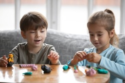 Little preschooler boy and girl children engaged in creative activity with playdough at home, small brother and sister play with modeling clay Play-Doh, do figures together, craft, hobby concept
