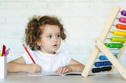 little preschooler girl learning math. kid studying on mathematical abacus. development, education, teaching and training of children. soft focus
