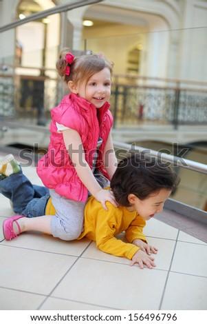 Little pretty girl and boy play on floor in big mall. Girl saddled lying boy.