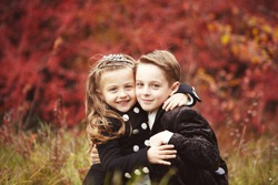 Little pretty girl and young boy hugging each other on autumn day. Brother and little sister cuddling. Happy family