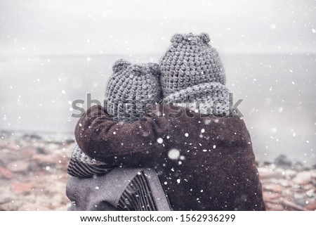 Little pretty girl in knitted grey hat hugging her frozen smaller brother during snowfall in winter, white cold weather, winter outside lifestyle close-up portrait Сток-фото ©