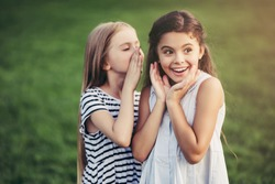 Little pretty girls having fun outdoor. Two cute girls are standing on green grass and telling a secret. Best friends.