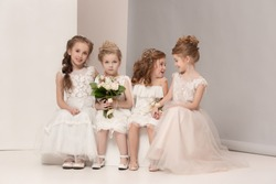 Little pretty girls with flowers dressed in wedding dresses. Lovely little girlfriends. girls dreaming of a wedding. Beauty, happiness, marriage, wedding style concepts. Studio shot