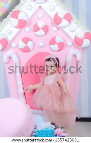 Little princes.little girl in pink dress studio with candy.